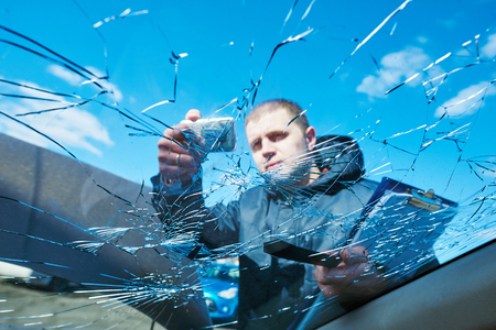 Insurance agent recording damage after car windscreen crash during inspecting damaged automobile on claim form Standard-Bild