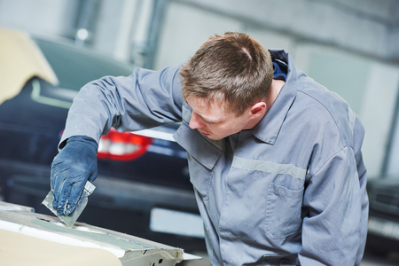 putty: Auto repair technology. repairman worker in automotive industry plastering or stopping car body before painting or repaint at automobile garage shop Stock Photo