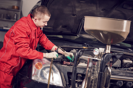 levels: Automobile engine oil replacement. Auto repair worker serviceman replacing lubricating motor liquid by pump at garage