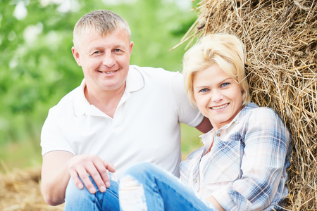 landlady: Happy adult young couple in love. Countryside with haystack
