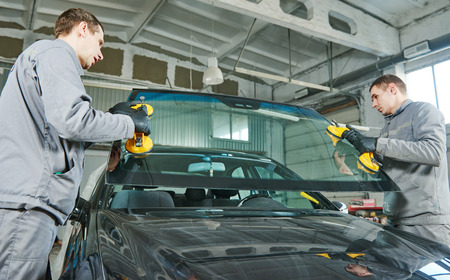 replaces: Glazier repairman mechanic worker replaces windshield or windscreen on a car in automobile workshop garage