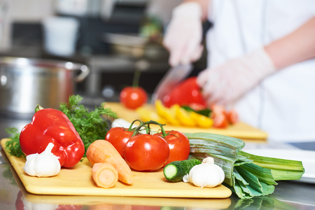 male cook chef hand preparing salad food dish on the desk in restaurant commercial kitchen