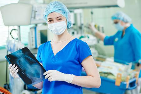 La cirugía y la unidad de cuidados intensivos. Mujer médico o enfermera con el retrato de imagen de rayos x en el hospital infantil quirúrgica