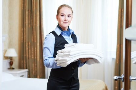 bedclothes: Hotel service. female housekeeping maid with towels and bedclothes linen in room Stock Photo
