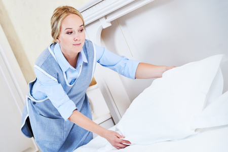 bedclothes: Hotel service. female housekeeping worker maid making bed with bedclothes or linen at inn room Stock Photo