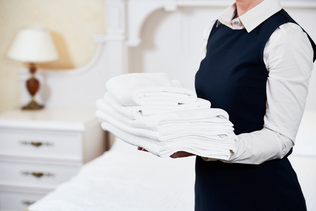 Hotel service. housekeeping maid with towels and bedclothes linen in room