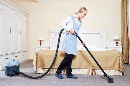 business service: Hotel service. female housekeeping maid worker with vacuum cleaner in room apartment