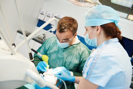 odontología de emergencia. médico dentista hombre y asistente femenina trabaja con el microscopio en el consultorio dental Foto de archivo