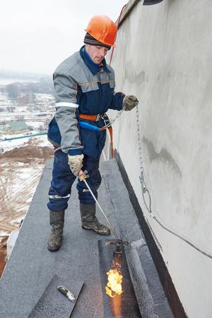 roofing felt: Flat roof installation. Heating and melting bitumen roofing felt