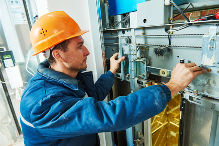 technician machinist worker at elevator mechanism installation or adjusting work of lift