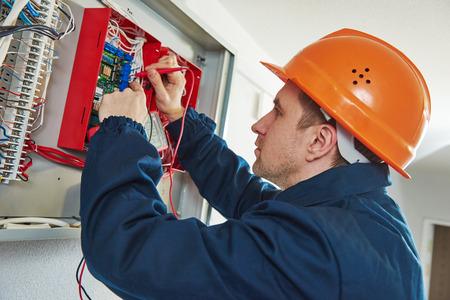 elektricien met schroevendraaier reparatie of het bevestigen van high voltage switching elektrische aandrijving in zekeringkast