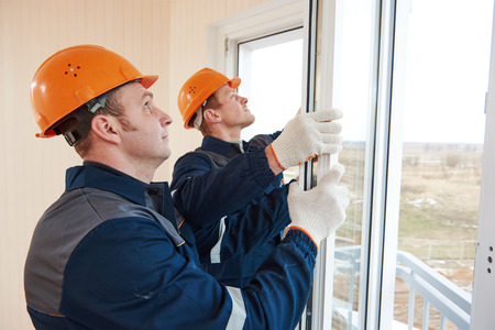 pane: two windows installation workers installing double-glass pane