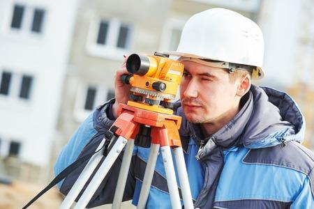 teodolito: El topógrafo trabaja con el equipo teodolito en el sitio de construcción