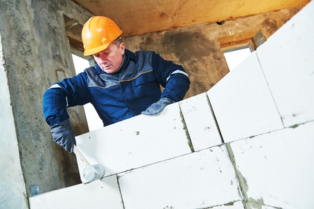 rennovation: Bricklaying construction work. bricklayer builder working with silicate brick
