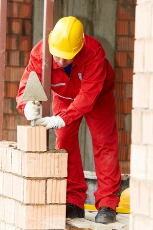 Bricklaying construction work. bricklayer builder working with red brick