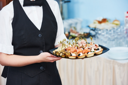 waitress catering service. female staff servicing dish full of snack food at restaurant event 스톡 콘텐츠
