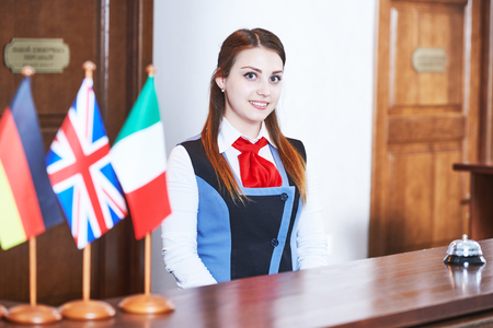 standing reception: Happy young female hotel receptionist manager worker standing at reception