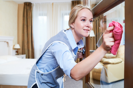 hotel staff: Cleaning service. Female hotel staff worker clean glass door from dust and spot