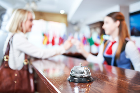 Hotel service. Female receptionist handing over electronic room key card to a client at the reception desk Stock Photo