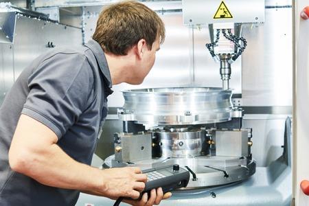 industria de mecanizado de metales. Trabajador o técnico de servicio de operación CNC fresado de la máquina en la fábrica