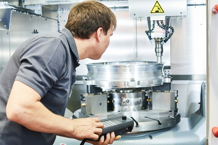 setup man: metal machining industry. Worker or service engineer operating cnc milling machine at factory