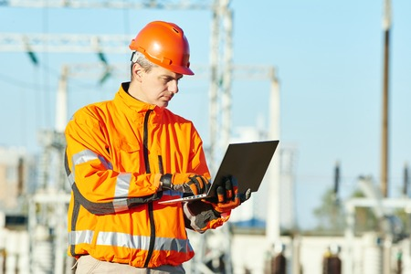 Engineering supervision. Male service engineer in high visibility reflecting clothing and hard hat working on notebook computer at heat electropower station