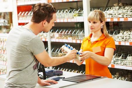 purchaser: Young woman help purchaser choosing plumber equipment in hardware shopping mall supermarket
