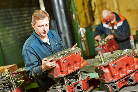 fettler: industrial worker assembler with gearbox utit at manufacture workshop in factory Stock Photo