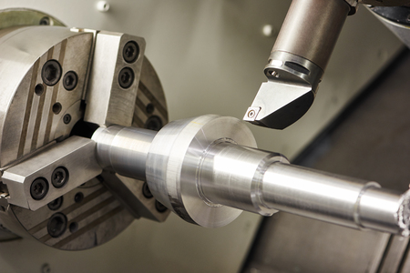 milling center: metalworking industry: cutting steel metal shaft processing on lathe machine in workshop. Selective focus on tool