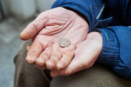 homeless person: Beggar people and human poverty. Male hands of homeless person with cent coin charity in city street