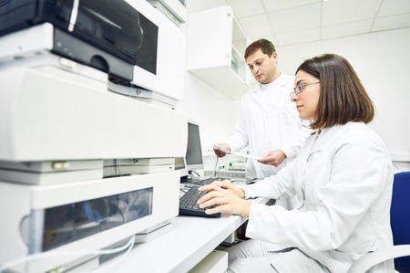 Pharmaceutical scientific researchers analyzing liquid chromatography data at pharmacy industry manufacture factory laboratory