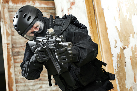 special agent: Military industry. Special forces or anti-terrorist police soldier armed with assault rifle ready to attack during clean-up operation