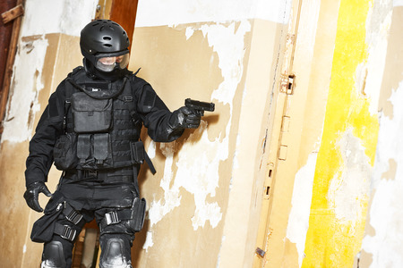 Military industry. Special forces or anti-terrorist police soldier, private military contractor armed with pistol ready to attack during clean-up operation