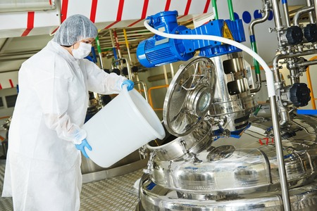 pharmaceutical worker with equipment mixing tank on production line in pharmacy industry manufacture factory Imagens