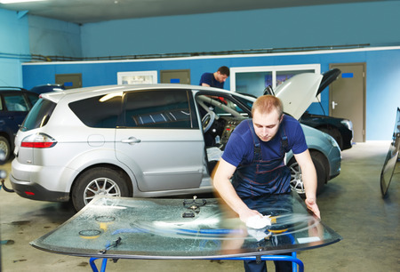 glazier: Automobile glazier cleaning windscreen or windshield of a car in auto service station garage before installation