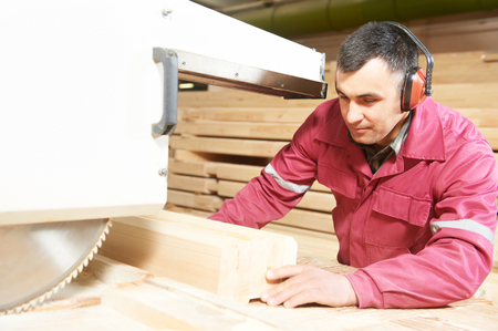 cabinet maker: process of carpenter worker with circular saw machine at wood beam cross cutting during furniture manufacture