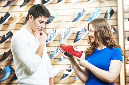 seller female assistant demonstrate shoes to young man during footwear shopping at shoe shop photo
