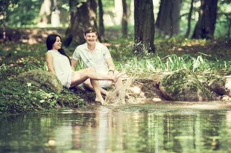 love park: Happy young couple in love having fun with water sitting on pond bank in park outdoors Stock Photo