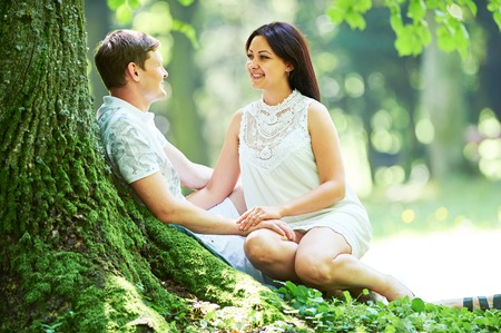Glückliche junge Paar in der Liebe im Park sitzen im Freien