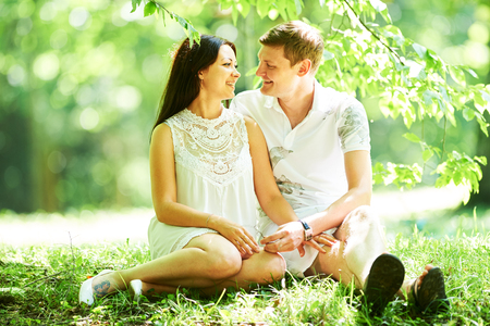Happy young couple in love sitting in park outdoors Stock Photo