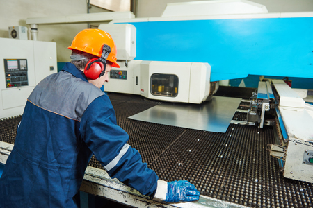 Industrial worker operator of metal bending and punching machine at factory