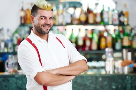 cheerful barman or bartender worker portrait standing in front of restaurant bar desk board