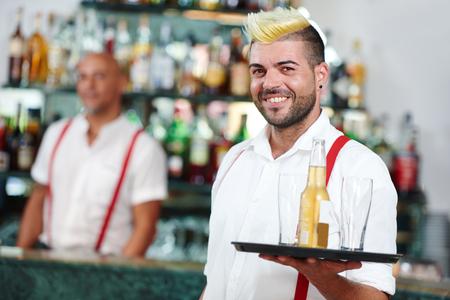 cheerful waiter or barman worker portrait standing in front of restaurant bar desk board Stockfoto