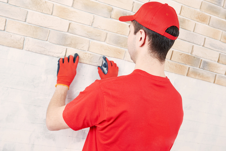 interior wall facing decorating work with brick veneer installing by professional construction worker bricklayer at home indoors photo