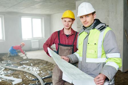 supervisión: constructor de capataz y trabajador de la construcción con el modelo que cubre piso discutir en el nuevo edificio de apartamentos o reparación de cubierta plana
