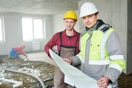 plasterer: foreman builder and construction worker with blueprint discussing floor covering in new building or repairing indoor flat apartment Stock Photo