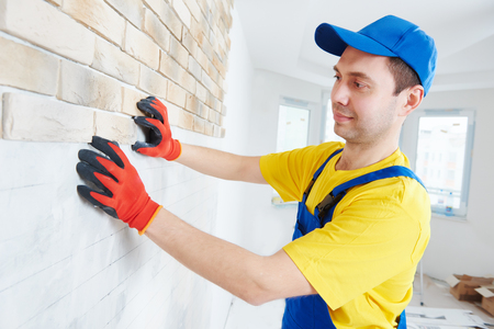 interior wall facing decorating work with brick veneer installing by professional construction worker bricklayer at home indoors