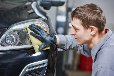burnish: Auto body repairs. Mechanic worker burnish and polishing automobile car headlight in garage workshop Stock Photo