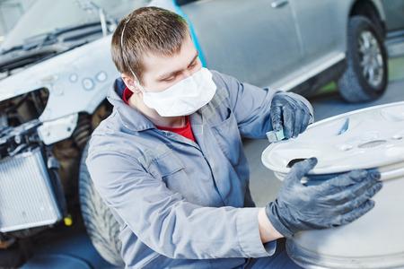light worker: Auto repair mechanic worker with light alloy car wheel disk rim during refurbish at garage service station.