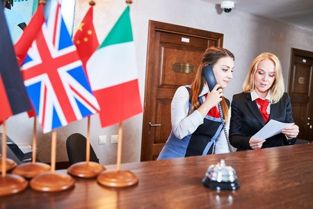 hotel staff: Hotel reception frontdest. young female frontdesk manager with receptionist worker staff Stock Photo
